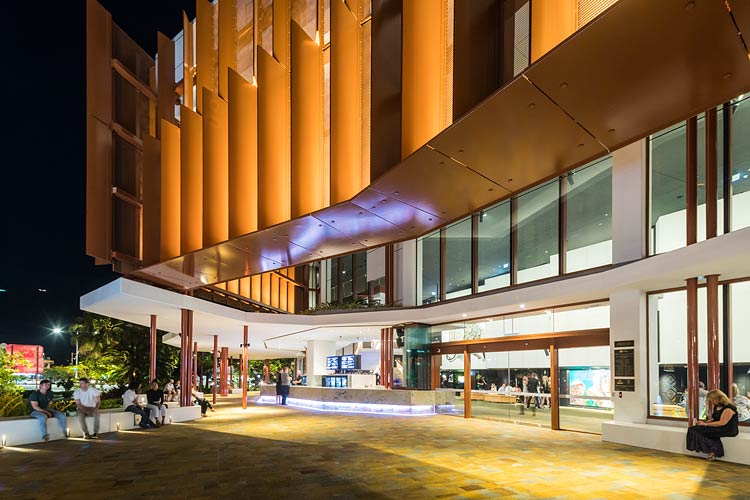 People sitting outside of the Cairns Performing Arts Centre at night