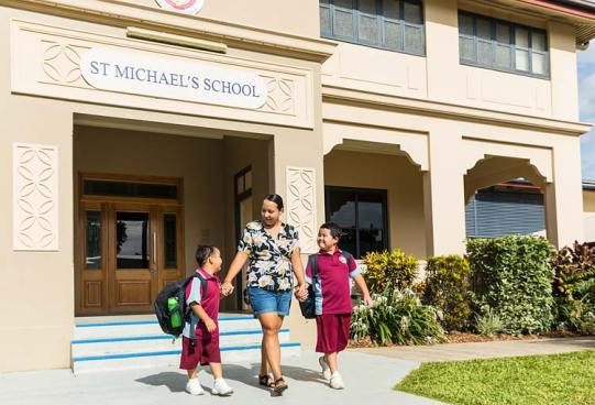 School parent walking with two young kids from entrance of school