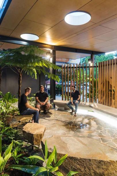 Men sitting talking in a yarning circle area at Bulmba-ja Arts, Cairns