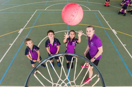 Group of young students and teacher learning to shoot at netball