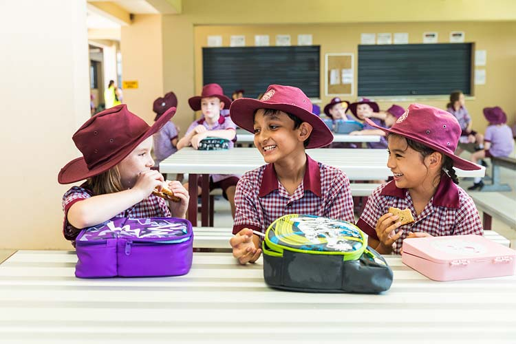 Group of school kids laughing and talking while eating lunch