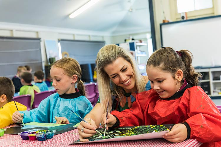 A teacher assisting a young student with a painting in art class
