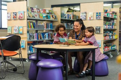 A teacher reading a book with indigenous students in the library