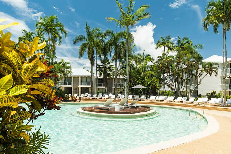 Resort swimming pool surrounded by palms and sun lounges