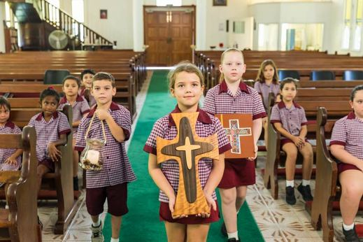 Young students conducting a religious mass in a Catholic school church