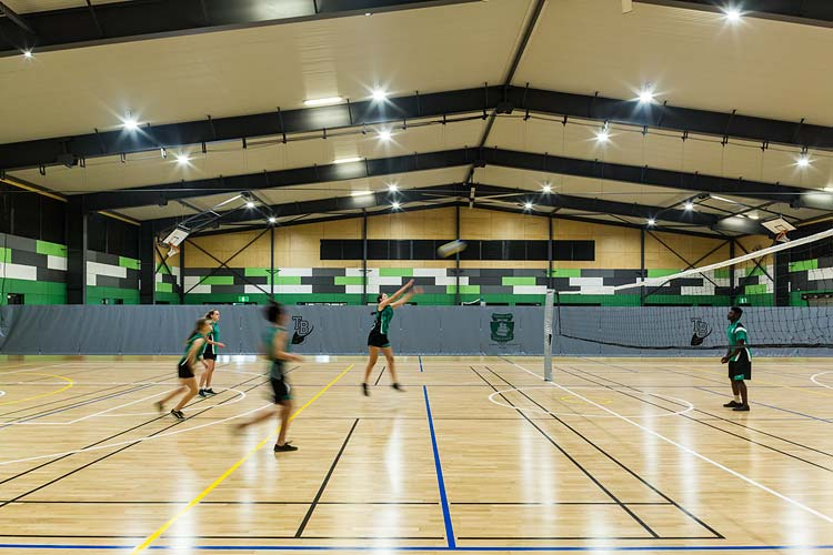 Interior of Trinity Bay High School multi purpose hall with kids playing game of volleyball