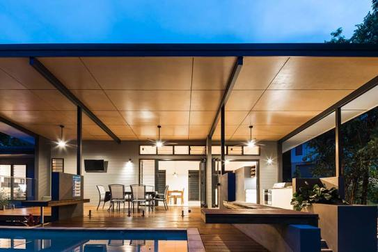 Pool and entertaining deck of residential home illuminated at twilight