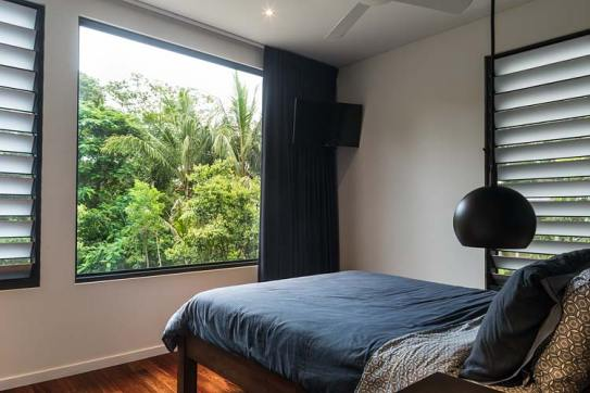 Bedroom interior with views out to rainforest surroundings