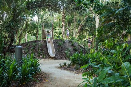 Kids on a playground slide surrounded by lush tropical foliage