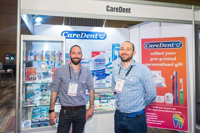 Two dental suppliers standing in front of booth at conference tradeshow