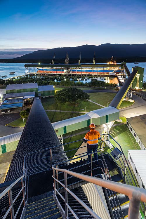 Twilight at the Cairns Bulk Sugar Terminal with worker looking out over cargo ship ready for loading