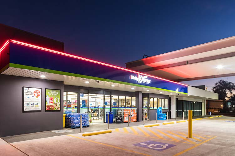 Exterior of Mobil service station convenience store illuminated at twilight