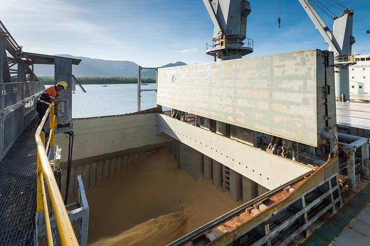 A worker monitors sugar being loaded into ship's hold at the Cairns Sugar Terminal