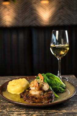 A restaurant dish of steak and prawns with garlic mash and broccolini