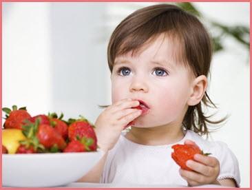 Девчушка ест клубнику