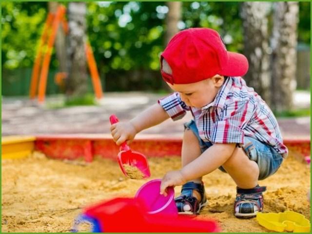 Играет малыш в песочнице