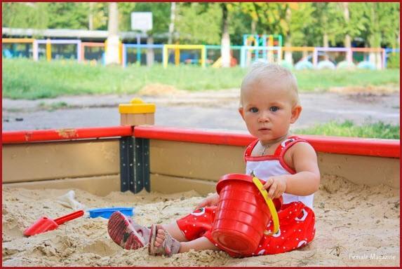 Малышка с ведёрком в песочнице