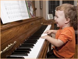 Малыш с радостью играет на пианино