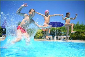 Дети прыгают в бассейн с бортика