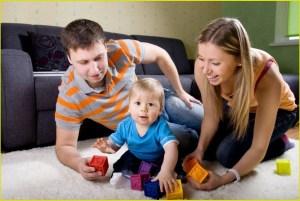 Молодые родители играют в кубики со своим малышом
