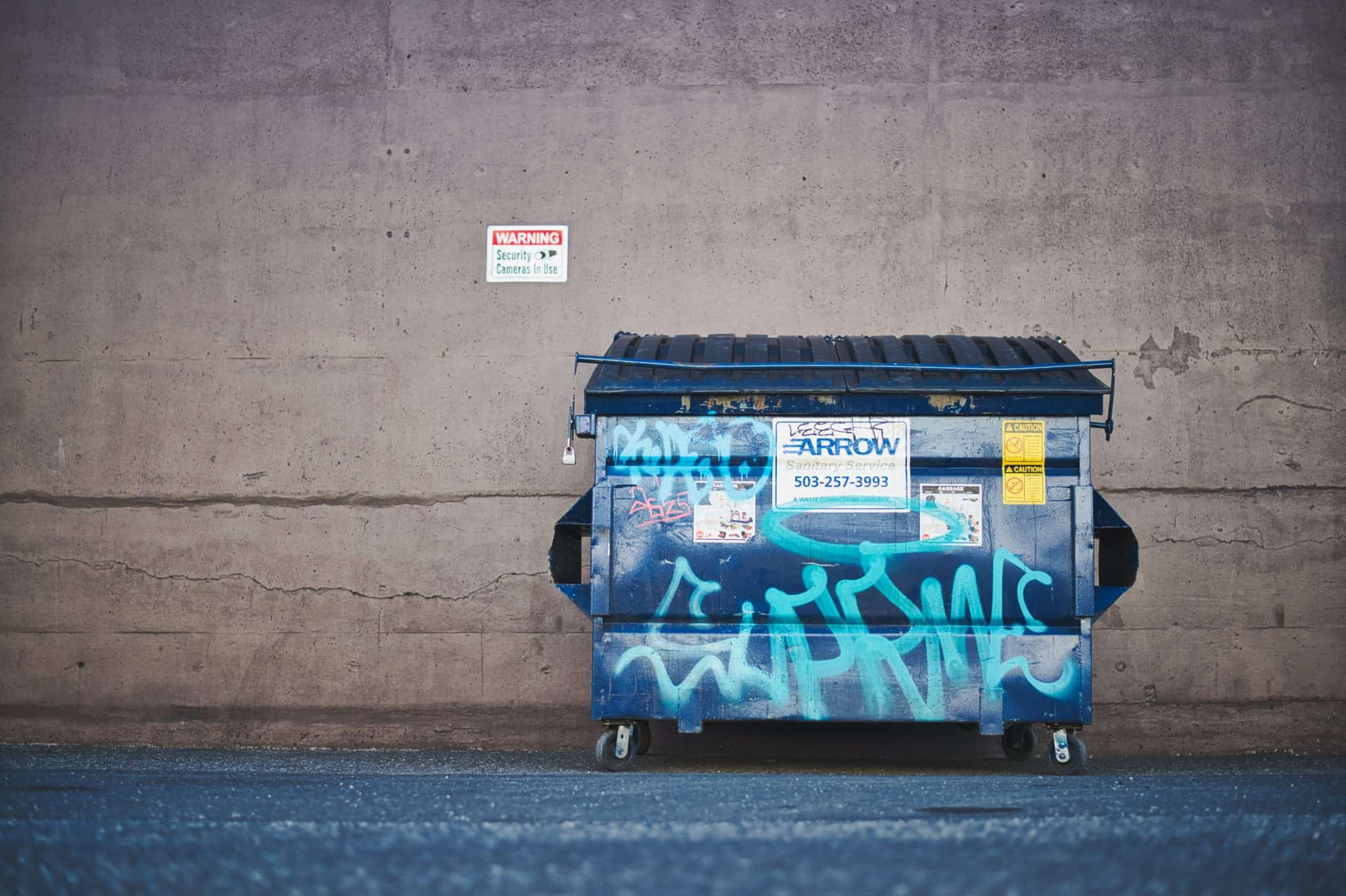 blue dump container in front of wall