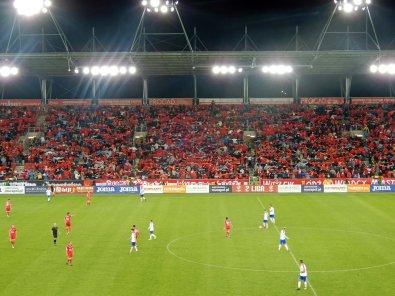 """Spielszene während die Fans im Hintergrund den """"Poznan"""" machen"""