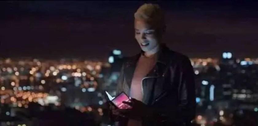 Uma mulher a segurar um telefone dobrável na frente de uma cidade à noite.