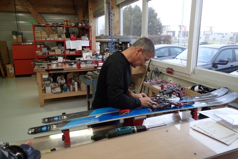 The ski tech ever so carefully working on Gra's skis
