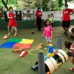 MADRID, SPAIN - JUNE 24: Teachers wearing protective face masks play with children in the playground at English For Fun school on June 24, 2020 in Madrid, Spain. English For Fun is a private school that works with preschool children (aged 1 to 6 years old) as well as enrichment classes for pre-teens (aged 7 – 14 years old). They have been offering online classes to support families during lockdown, and after restrictions were eased and the spread of Coronavirus declined, they opened their doors on Monday 22nd offering Urban Summer Camps for kids. With the end of the state of alarm, the Government has announced that pre-schools can reopen from July 1st, but only as an option for parents that can't work from home, so many parents are using alternatives like private Urban Summer Camps like English for Fun as a solution. The school's staff have put into place many safety measures, such as regular supervised handwashing, temperature checks on arrival, regular ventilation of classrooms and enhanced cleaning regimes to keep pupils and staff as safe as possible. (Photo by Pablo Cuadra/Getty Images)