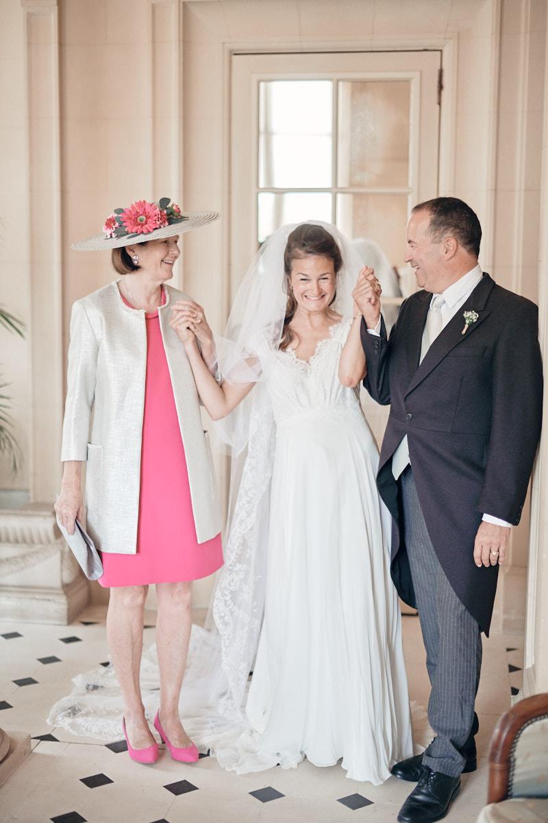 les parents de la mariée l'accompagnent avant la descente de l'escalier