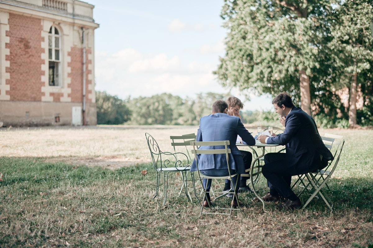 des invités sur une table de jardin à l'ombre des arbres bordant le chateau de craon