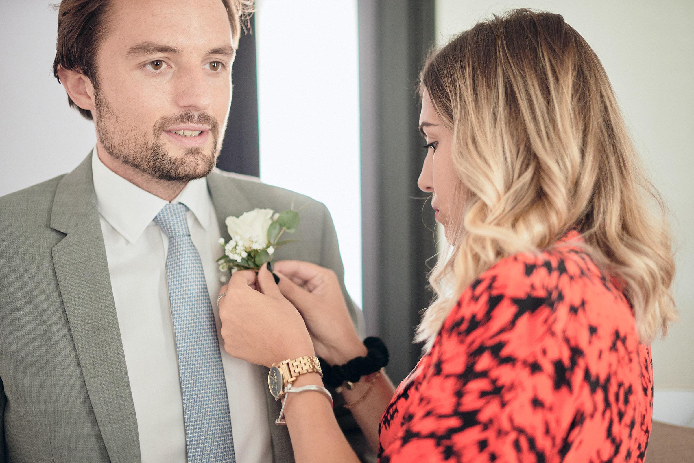 une amie accroche la boutonnière sur la veste du marié