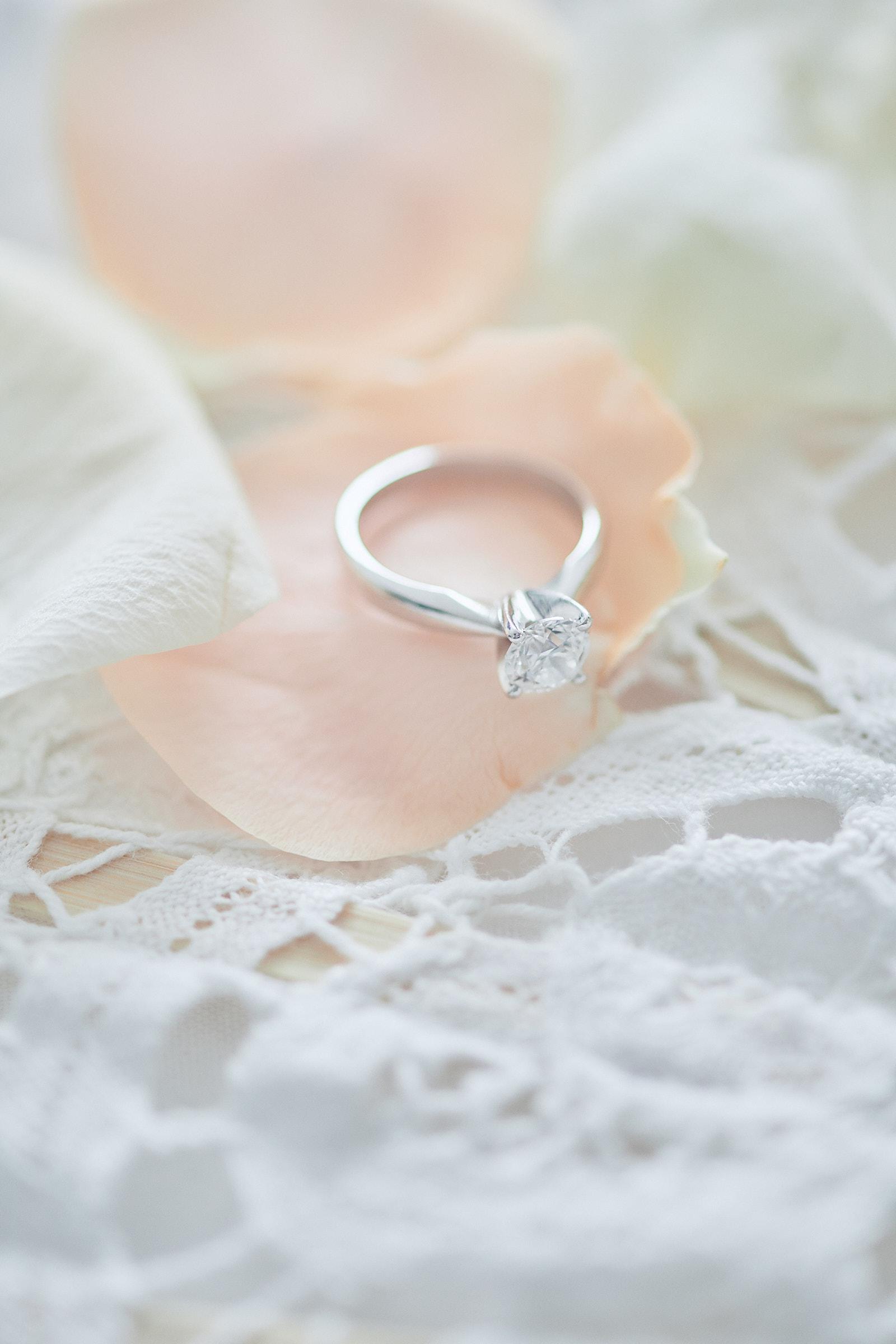 bague de fiançailles sur pétales de roses et éventail