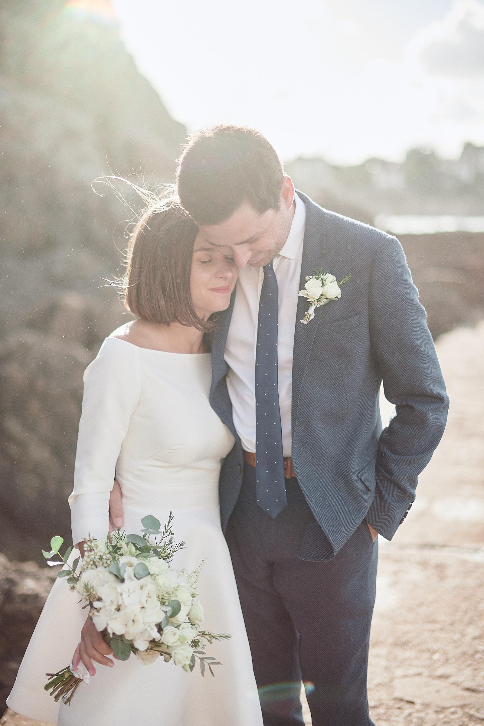 les mariés se serrent l'un contre l'autre sur le chemin de ronde du moulinet à dinard