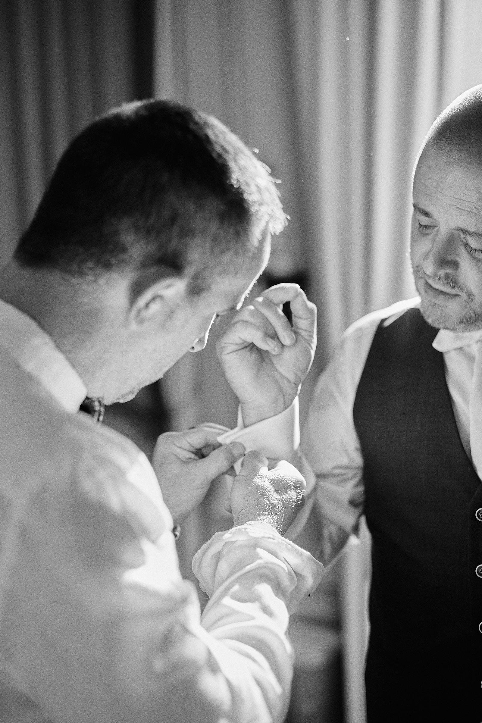 un témoin du marié attache un bouton de manchette