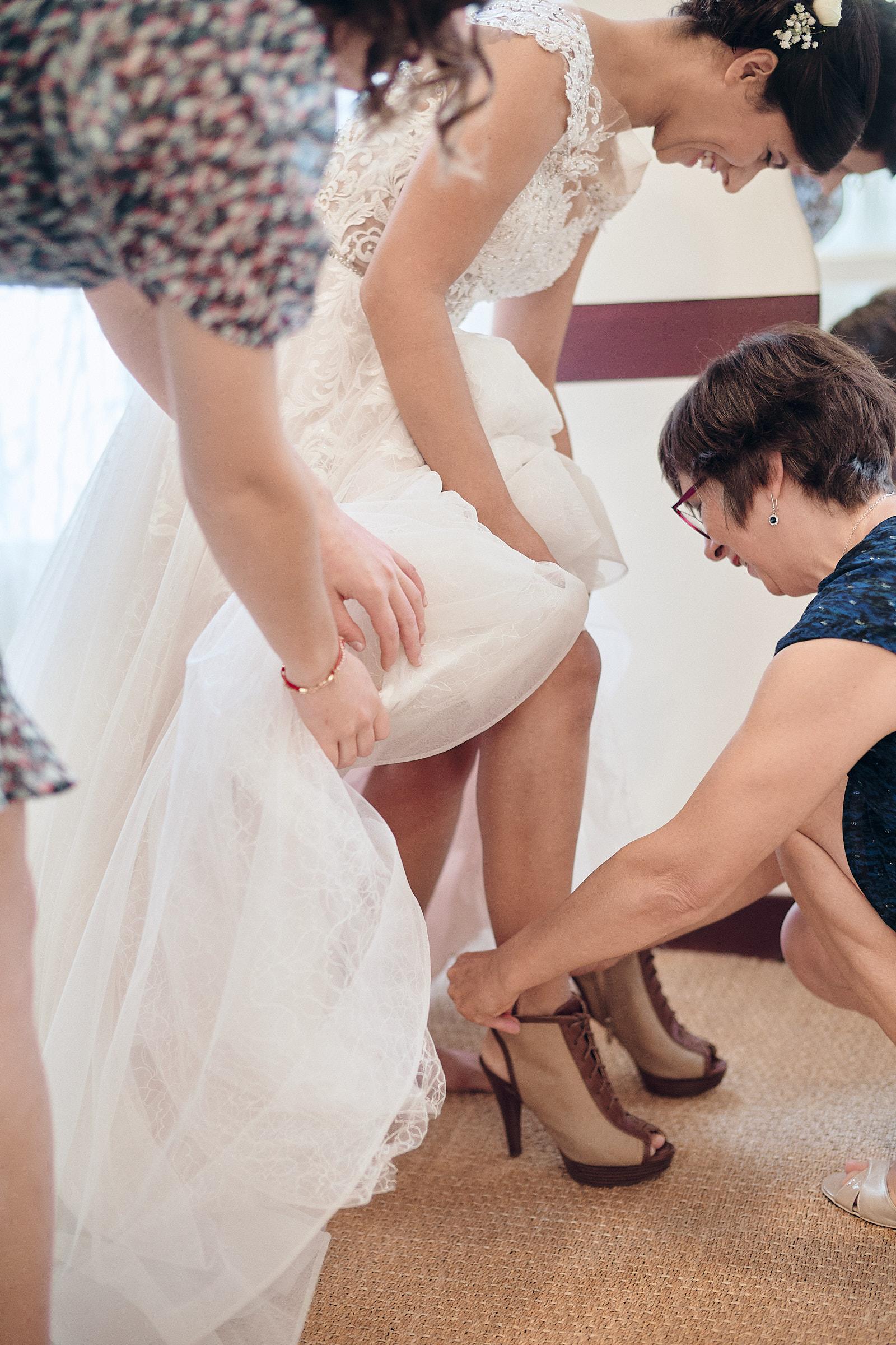 la mère du marié aide la mariée à mettre ses chaussures