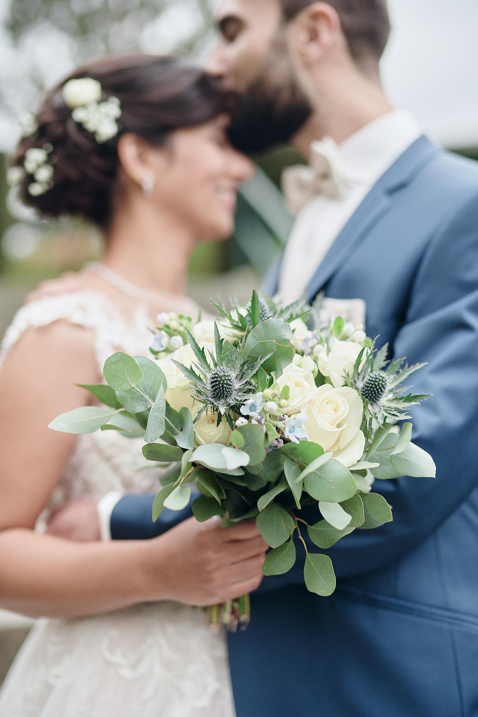détail sur le bouquet pendant que les mariés s'embrassent