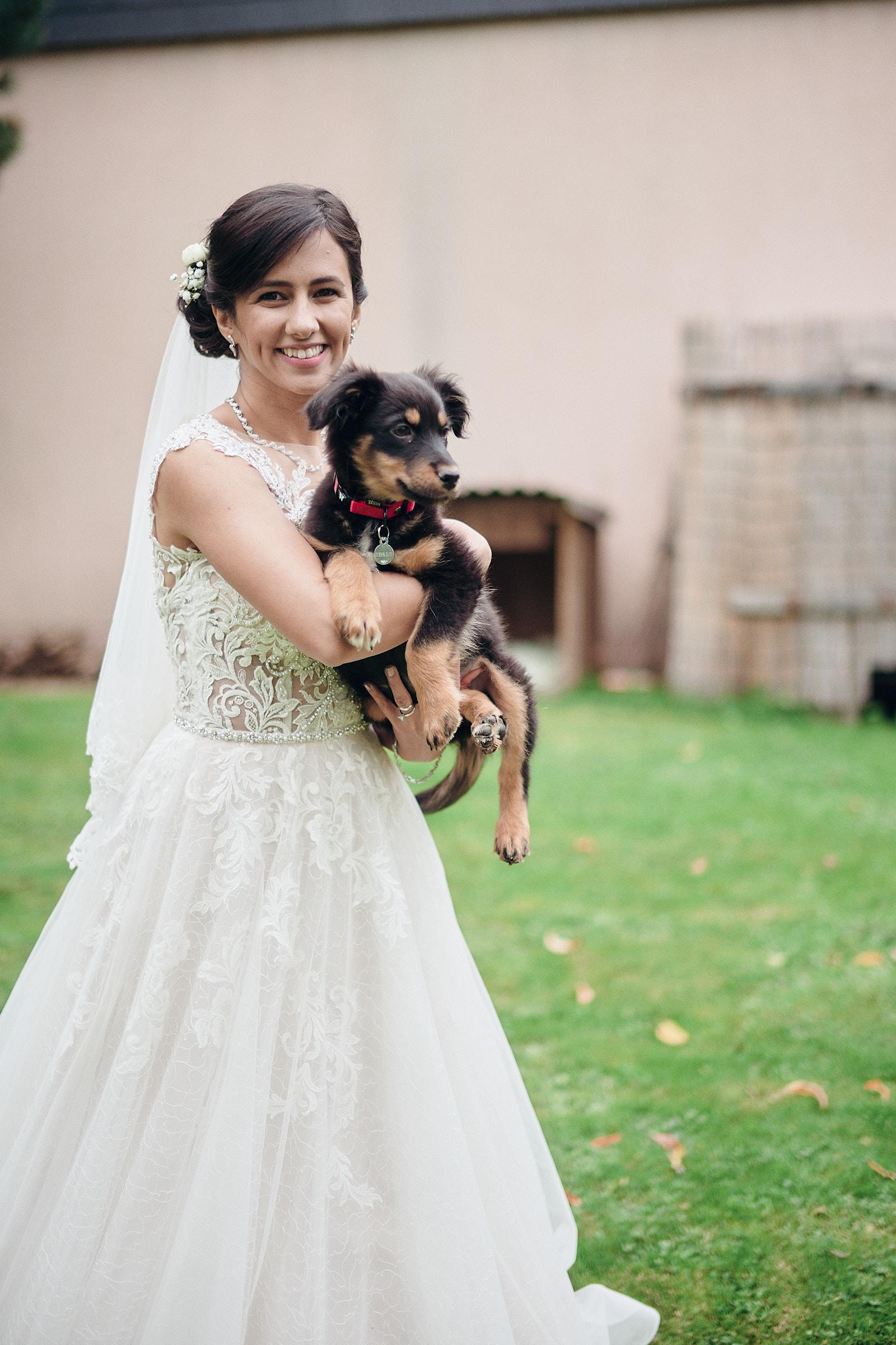la mariée porte un chiot dans ses bras
