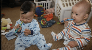 Twin babies brushing teeth