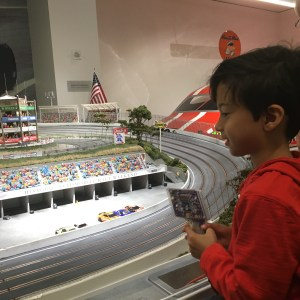 Racing cars on a track with kids at the Le May America's car museum