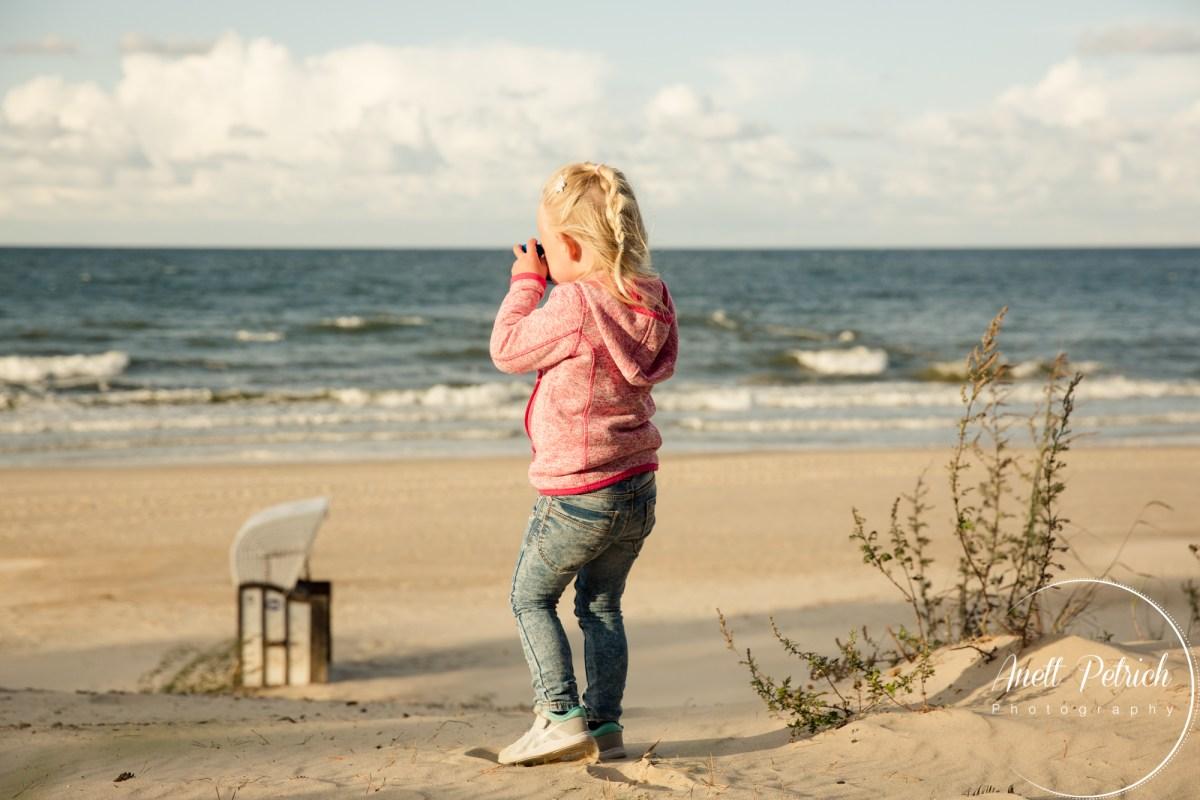 kleines blondes Mädchen fotografiert die Ostsee