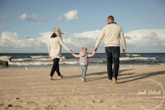 Familie geht am Strand spazieren, die Eltern halten die Hände der Tochter