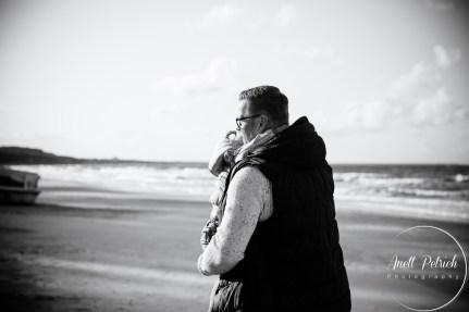 Mann trägt kleines Mädchen auf dem Arm und geht am Strand entlang