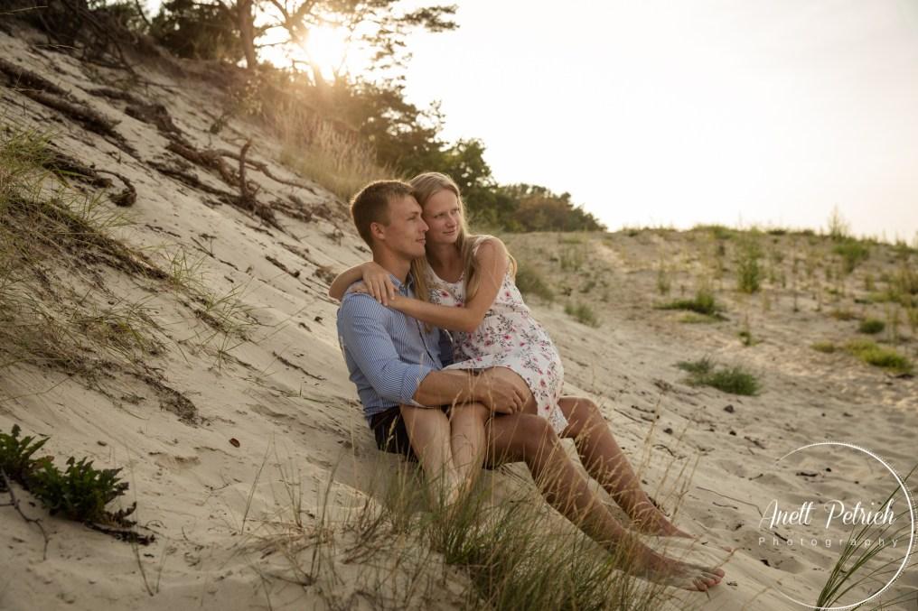 Paarshooting am Strand die Frau sitzt auf dem Schoß des Mannes, sie sitzen beide in den Dünen und schauen zum Meer