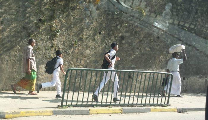 Mænd i saronger og skolebørn i hvidt tøj