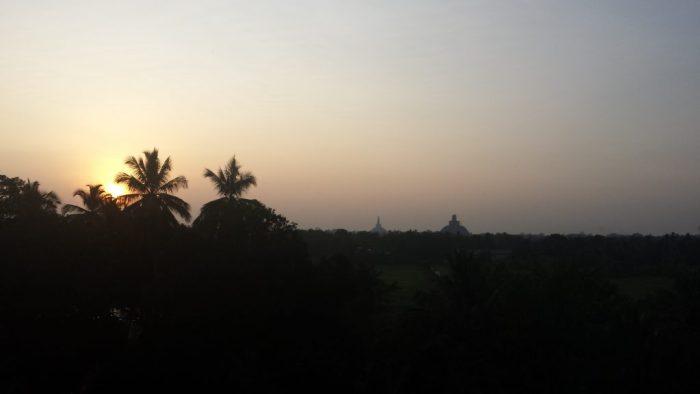 Solnedgang med stupaer i baggrunden