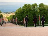 The guards line up, two by two, next to each flagpole, all the way down the palace grounds to Karl Johans Gate.