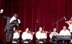"""The boys in the Hungarian Folk Ensemble Orchestra got a chance to show off, too, with a dance number called """"Four Men from Transylvania."""" Each guy highlighted a different dance style and costume from the region. By the way, note the musician playing the thing that looks like a piano. It's called a cimbalom, and its closest kin is actually a hammer dulcimer. (Its strings are struck by hand with padded mallets.) Historically, upper-class kids get cimbalom lessons rather than piano lessons. It's one of the oldest and most traditional of Hungarian instruments."""