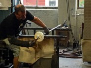 Here, a glassblower has disconnected his piece from the blowpipe. While the glass is still hot, he's reattached it to a long metal punty rod. He then rolls the rod across the bench while shearing off the excess glass left behind by the blowpipe.