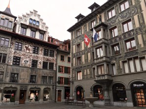 "Hirschenplatz (""Deer Plaza,"" named after a restaurant that serves deer) hosts two gorgeous buildings. The images on Dornach House (left) celebrate the 400th anniversary of the Swiss over the Germans at the Battle of Dornach in 1499. The building on the right is adorned with a series of huge diamond rings advertising the original owner's profession (he was a jeweler.)"